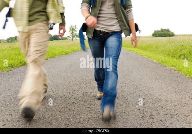 Close-up blurred portrait hiking couple legs backpack on asphalt road - Stock Image