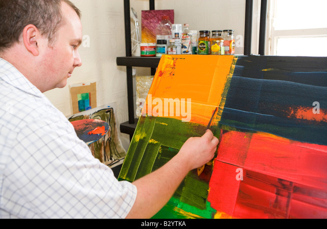 artist working on an abstract painting with a knife or trowel - Stock Image