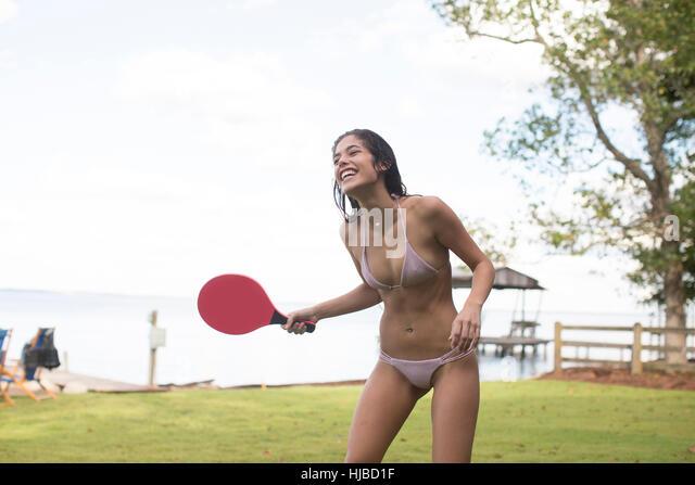 Young woman in bikini playing table tennis at coast, Santa Rosa Beach, Florida, USA - Stock Image