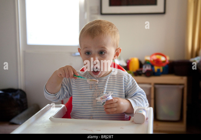 Young boy 16 months old eating a messily eating yogurt. Hampshire, England. - Stock Image