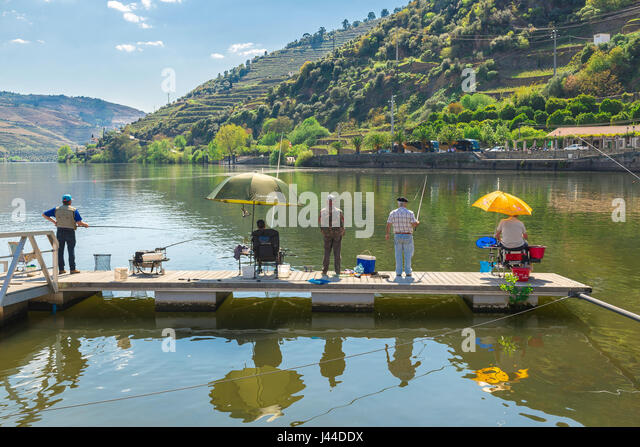 Men fishing, a group of middle aged men fishing in Portugal, Europe. - Stock Image