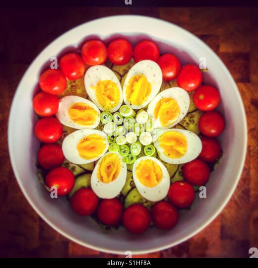 Salad bowl with eggs, tomatoes and salad onions - Stock Image