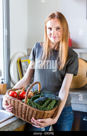 Woman with a basket of vegetables. - Stock Image