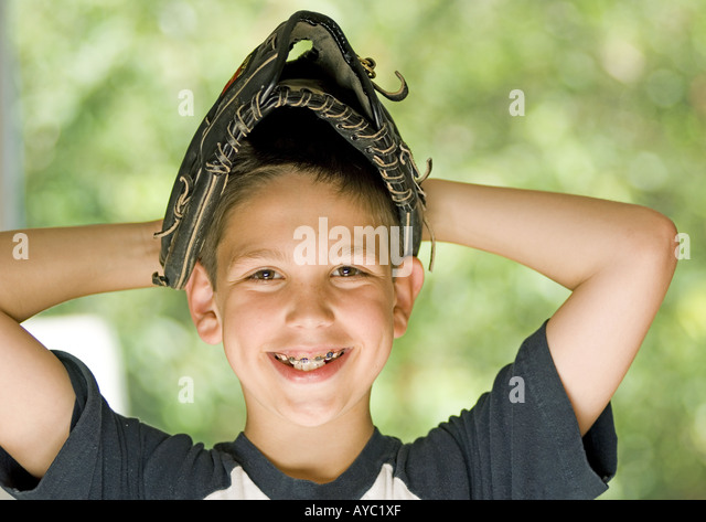 Smiling boy wearing baseball glove on his head - Stock Image
