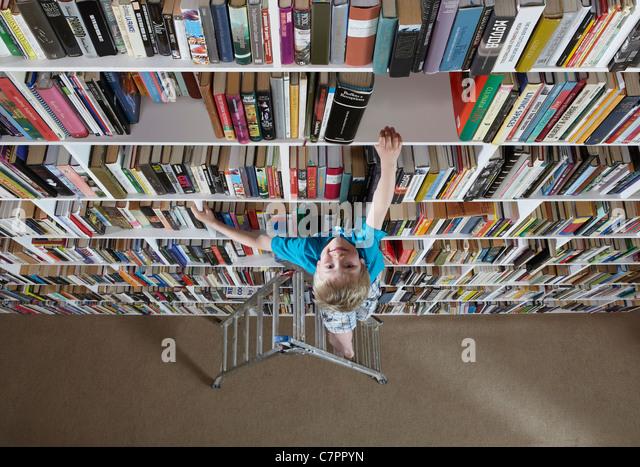 Boy using stepladder on bookshelves - Stock Image