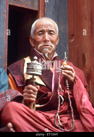 Monk counting bead and rotating prayer wheel NO MR - Stock Image