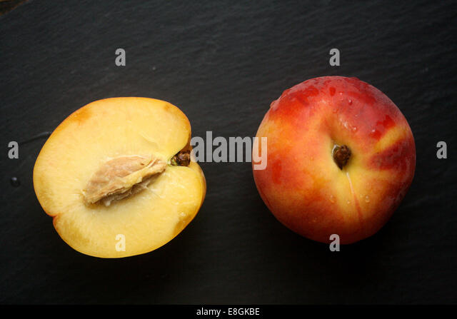 Fresh peach and halved peach - Stock Image