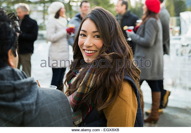 Portrait of smiling woman in scarf on patio - Stock Image