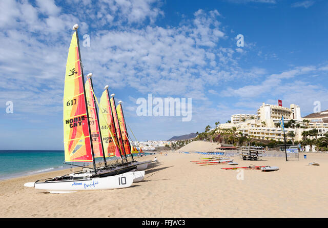 Hobie cats and wind surfers beached on the sand at Morro Jable, Fuerteventura, Canary Islands, Spai - Stock Image