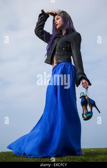 Young woman holding her shoes while looking into distance - Stock Image