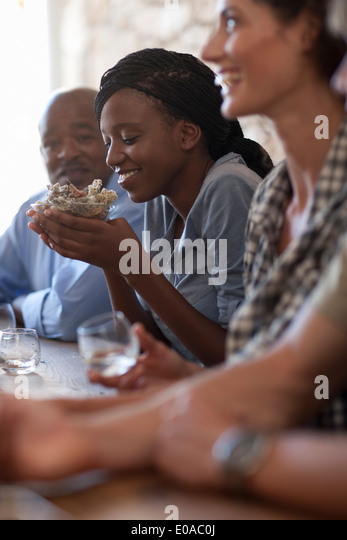 People sitting around table, tasting drinks - Stock Image