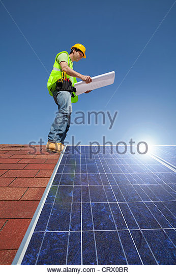 Engineer examining blueprint on rooftop with solar panels - Stock Image