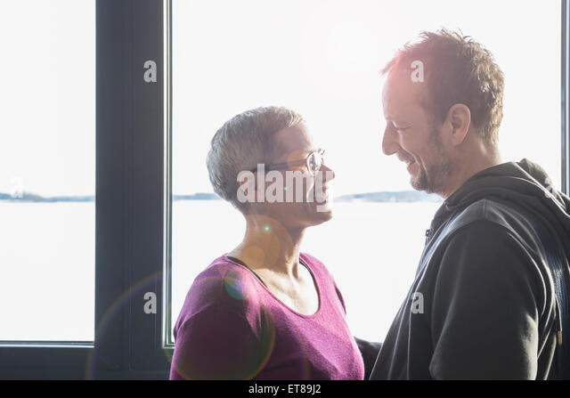 Side profile of a couple looking at each other and smiling, Bavaria, Germany - Stock-Bilder
