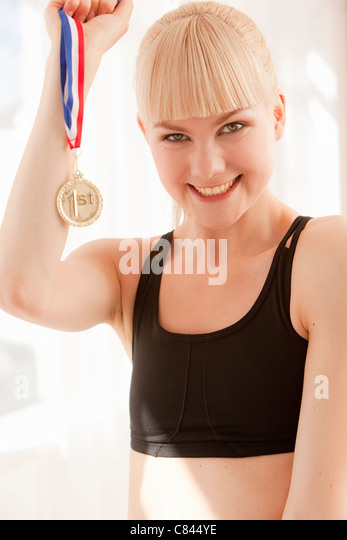 Cheering athlete holding gold medal - Stock Image