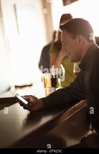 Businessman looking at cellphone in a wine bar - Stock Image