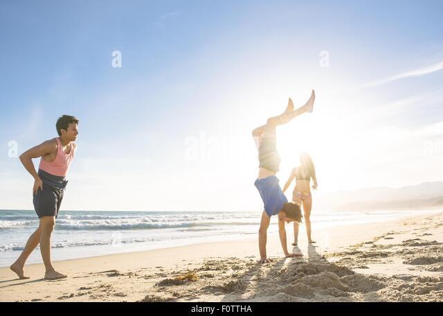 Group of friends fooling around on beach - Stock-Bilder