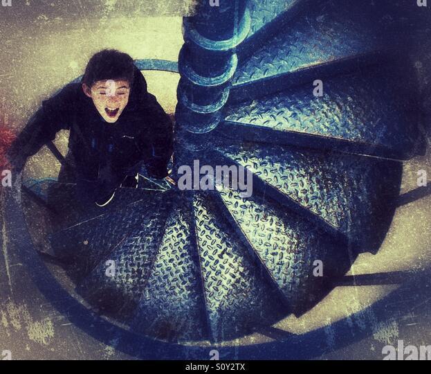 Eyes shut. Young boy walking up metal steps . - Stock Image