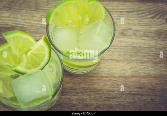 Still life of lime infused drinks on wood table top. - Stock Image