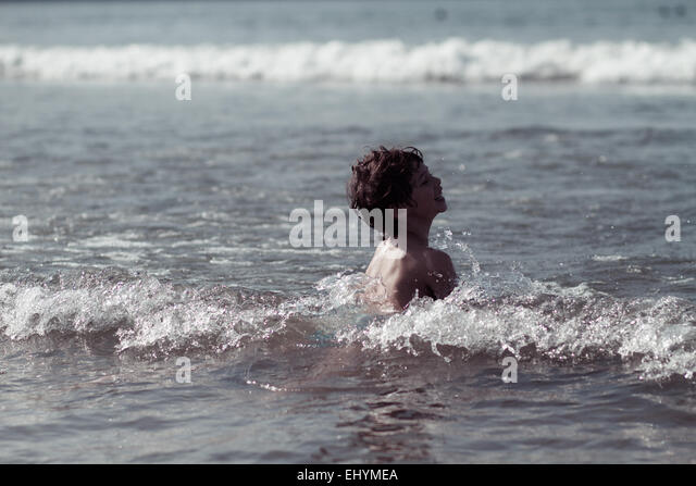 Boy playing in the surf, Brazil - Stock Image