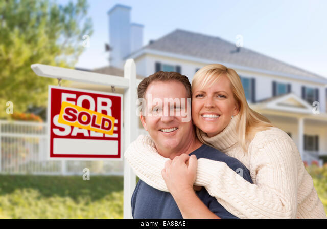 Affectionate Happy Couple in Front of New House and Sold For Sale Real Estate Sign. - Stock Image