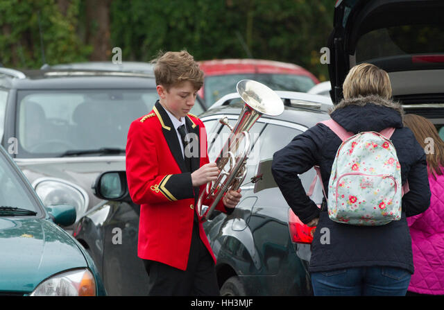 Young member of the Woodford Excelsior brass band prepares for a Remembrance Day parade - Stock Image