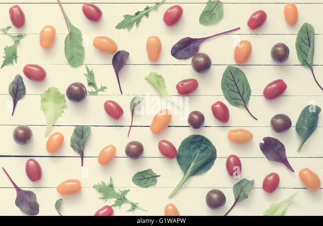 Food flat lay. Pattern of fresh greens and vegetables on white wooden background. Healthy eating concept - Stock Image