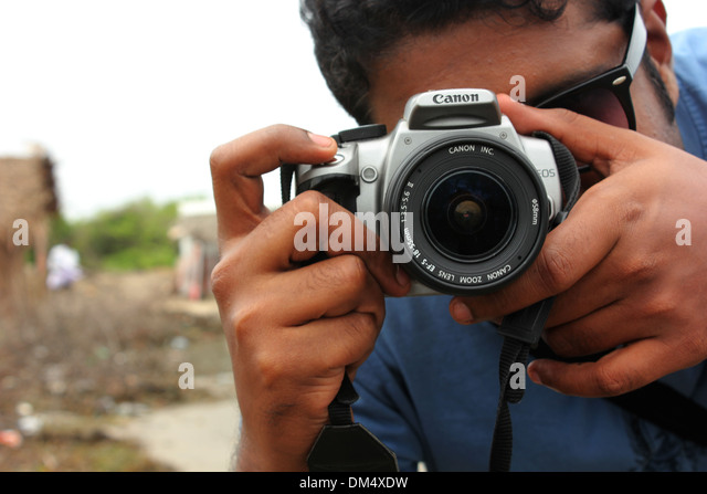 A young Indian taking picture using a DSLR camera - Stock Image