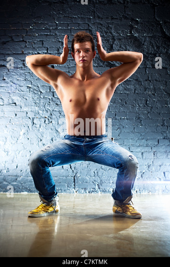 Young man sports exercises. On wall background. - Stock-Bilder
