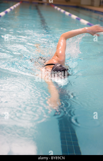 A woman swimming laps in an indoor pool - Stock Image