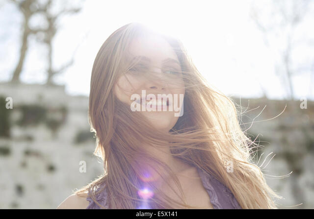 Happy young woman in sunlight, hair blowing over face - Stock Image