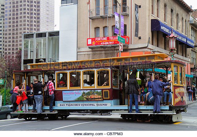 California San Francisco Chinatown Grant Street transit system cable car passenger exterior holding on outside railing - Stock Image