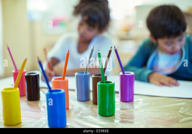 Colored pencils on desk in classroom - Stock Image