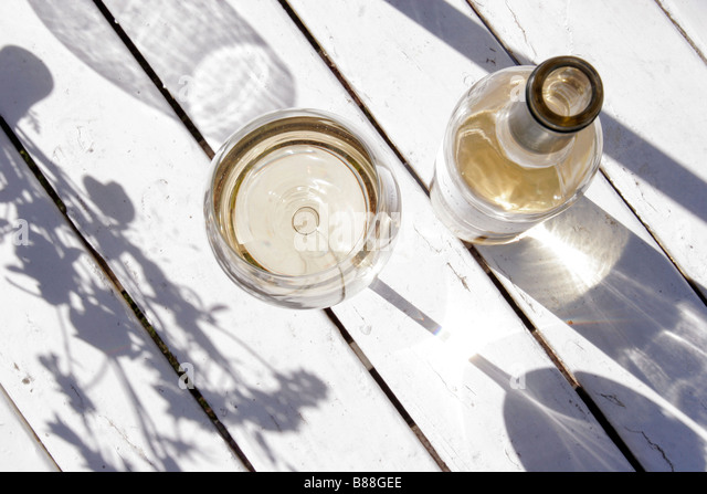 A bottle of white wine and a glass placed outside on a white wooden table. - Stock-Bilder