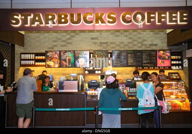 China Beijing Dongcheng District Nanluoguxiang hutong historic shopping Starbucks Coffee cafe counter customers - Stock Image