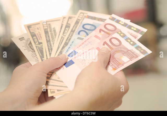 Female hands holding American, British and European bank notes - Stock Image