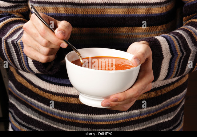 Ladies hands holding bowl of tomato soup - Stock Image