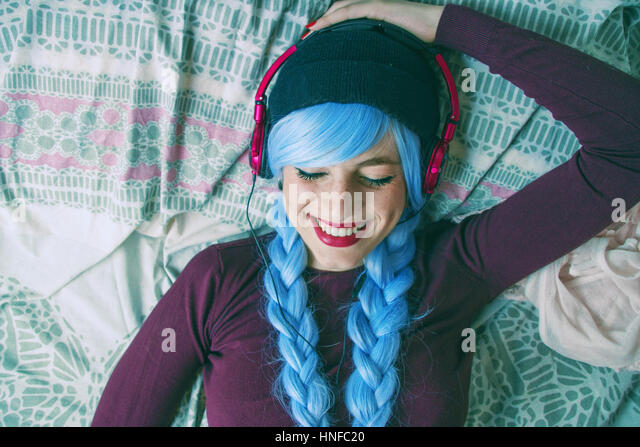 Alternative teenager with blue hair listenig to music - Stock Image