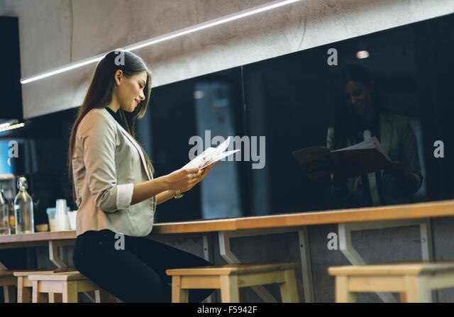 Beautiful woman reading the menu on a counter of a bar - Stock Image