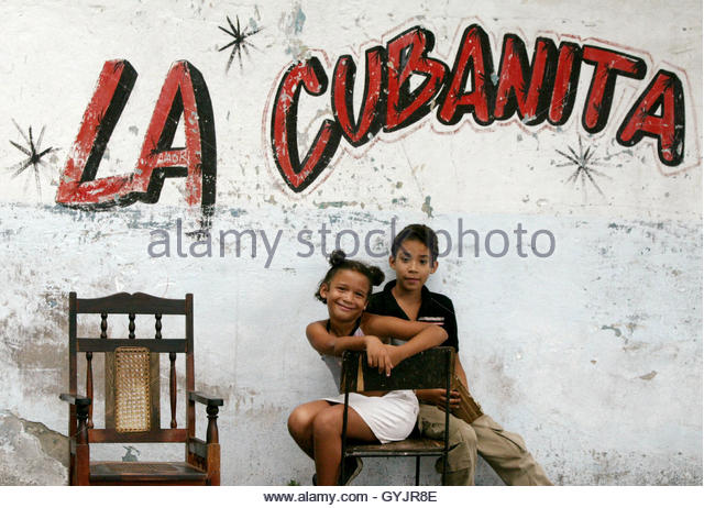 Cuban children sit on a chair on the street prior to a dancing parade in Santiago de Cuba, July 25, 2003. [While - Stock Image