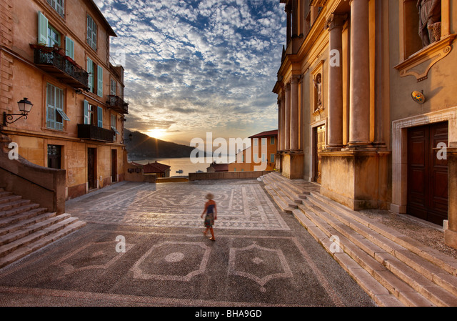 a woman walking through Parvis St Michel at dawn, the Old Town, Menton, Cote d'Azur, Alpes Maritime, Provence, - Stock-Bilder