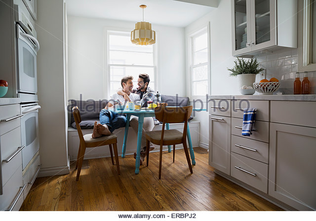 Homosexual couple hugging at breakfast table - Stock Image