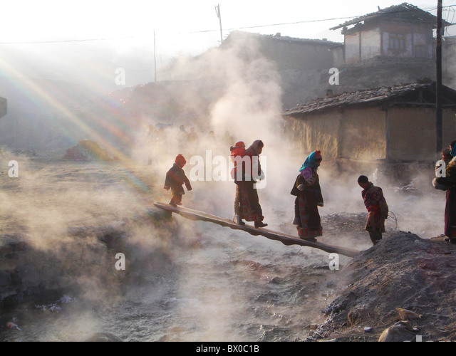 Tibetan people crossing the hot spring by a narrow wooden board, Langmu Monastery, Gannan, Gansu, China - Stock-Bilder