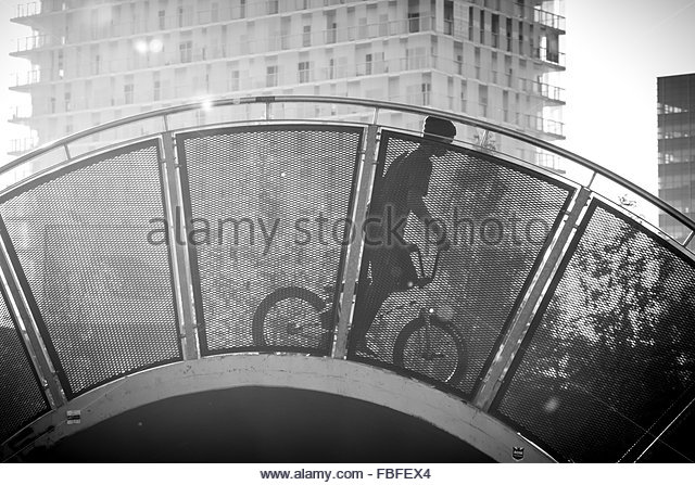 Low Angle View Of Boy Riding Bicycle On Bridge Against Building - Stock-Bilder