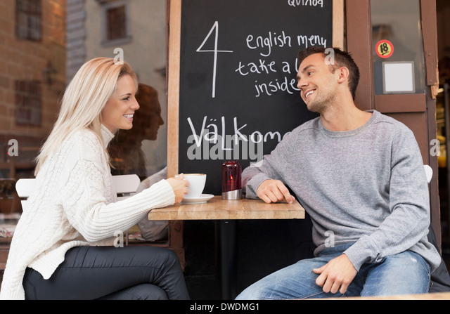 Young couple spending leisure time at outdoor cafe - Stock Image