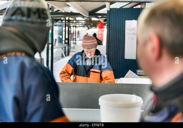 Fishermen looking at male colleague working in industry - Stock Image