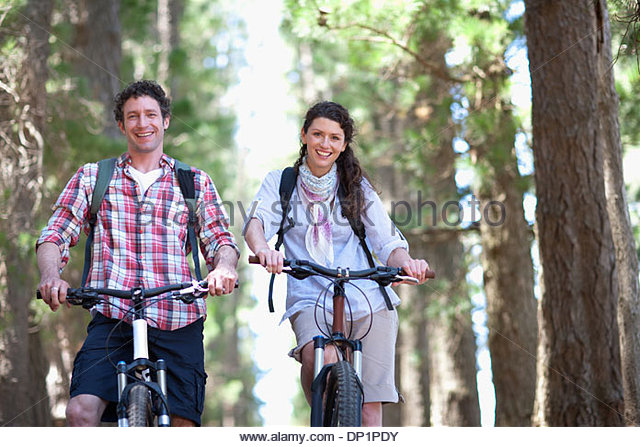 Couple riding bicycles in woods - Stock Image