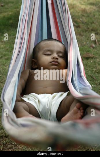 1 year old Asian baby sleeping on a hammock - Stock Image