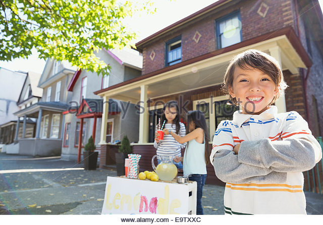 Portrait of confident boy at lemonade stand - Stock Image