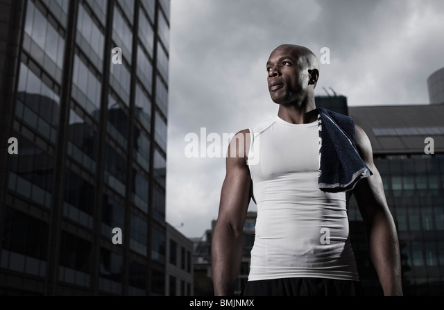 Fit man wearing sportswear backgrounded by modern city buildings - Stock-Bilder