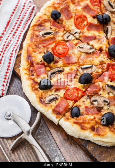 Pizza with ham, mushrooms and olives - Stock Image
